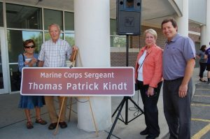 Mr. Ruffing and members of the Kindt family with the sign honoring Thomas Patrick Kindt '58