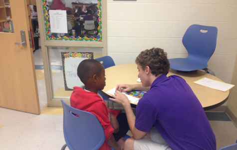 Senior Evan Mullaney helps second grader Kevin Martin with his reading