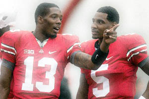 Quarterbacks Braxton Miller and Kenny Guiton tallk on the side line