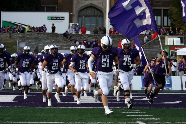 Senior Joe Schroer leads the men of Elder on to the field for the first game of the 2015 season against neighborhood rival Oak Hills.