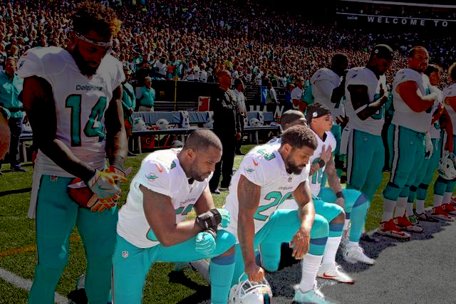 Miami Dolphins Players kneel during the Anthem.