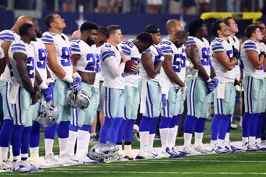 The Cowboys all stand for the National Anthem after a spark from owner Jerry Jones.
