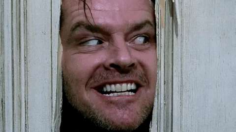 Jack Nicholson peers through the cracked door towards his wife in The Shining
