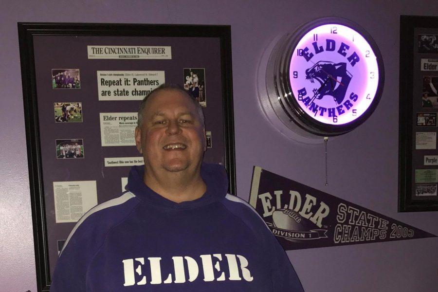 A proud Jim Gardner stands beside Elder memorabilia in his Elder-themed basement.