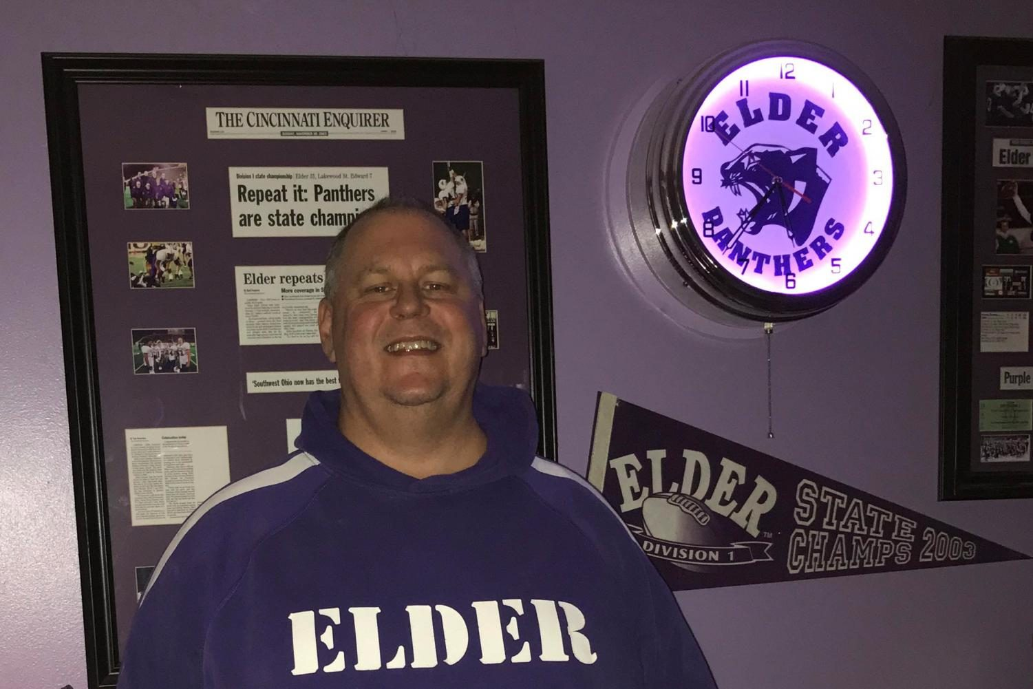 A proud Jim Gardner stands beside Elder memorabilia in his Elder-themed basement.