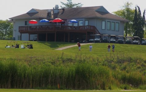 Golfers tee off on hole 10 in front of the club house