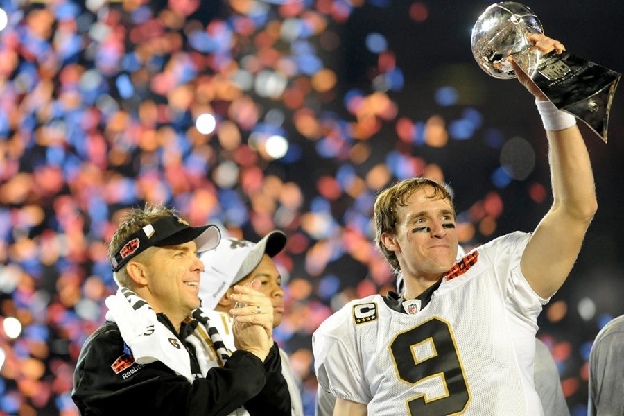 MIAMI GARDENS, FL - FEBRUARY 07: Drew Brees of the New Orleans Saints holds up the Lombardi Trophy on the podium as head coach Sean Payton looks on after defeating the Indianapolis Colts in Super Bowl XLIV on February 7, 2010 at Sun Life Stadium in Miami Gardens, Florida.  (Photo by Rob Tringali/Sportschrome/Getty Images)