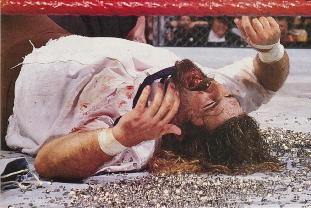 Mick Foley after getting choke slammed onto tacks