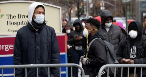 People wait in line to be screened for the coronavirus at the Brooklyn Hospital Center, New York, March 19, 2020.