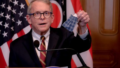 Mike DeWine holding up a cloth mask while giving a speech about Covid-19