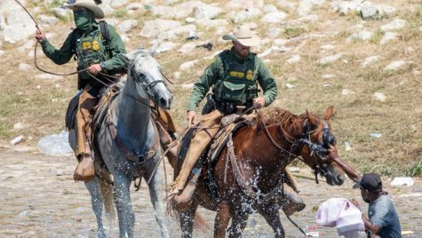 Agents of the Border Control seen holding people back with whips